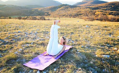 Женщина выполняет упражнения на природе