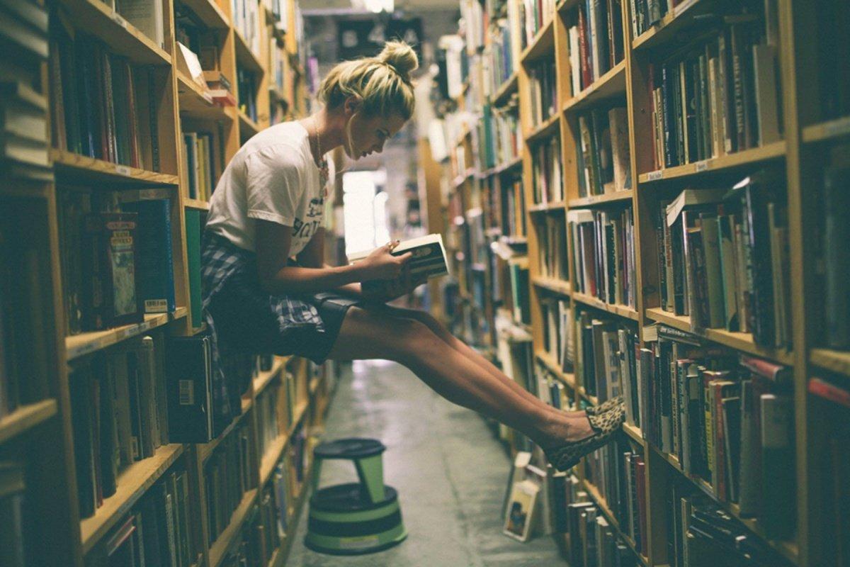 Девушка читает в библиотеке