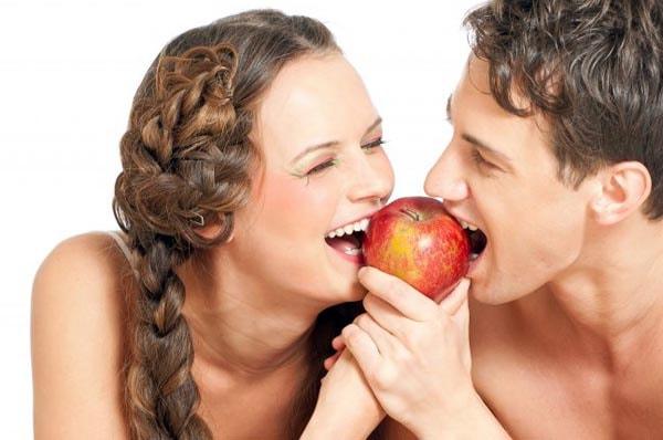 Девушка с парнем кушают яблоко