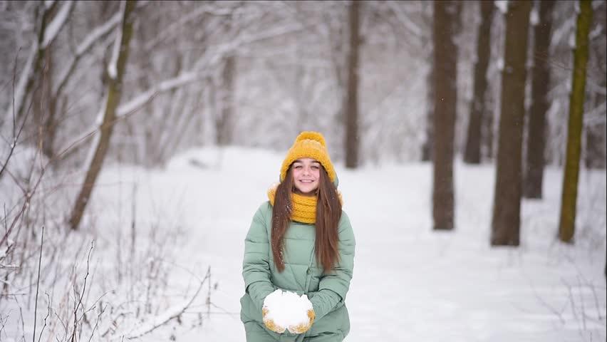 Девушка в желтой шапке посреди снега.